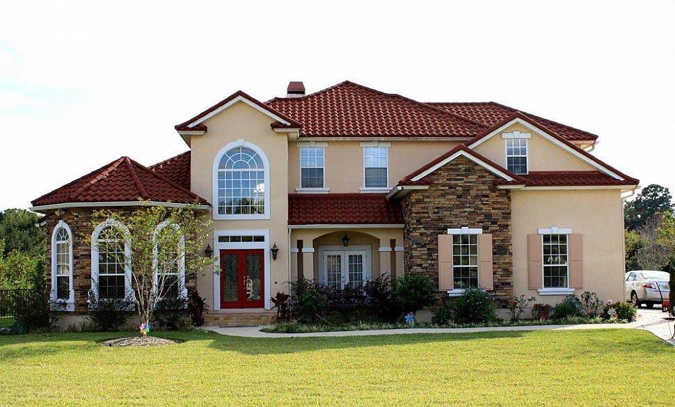 Гостеприимный дом с газоном, клумбой и керамической черепицей
